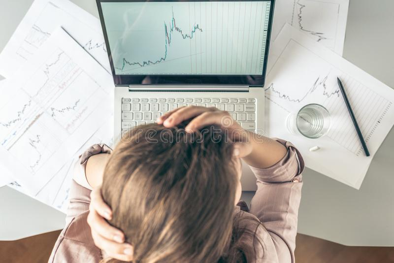 Top view. Tired business woman with headache at office with glass of water and pill on the background of graphics and charts print royalty free stock photo
