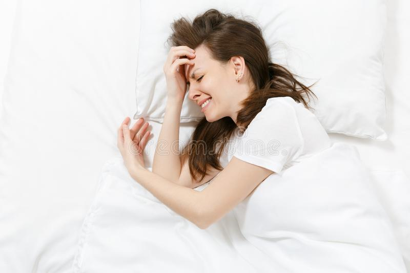 Top view of tired stressed crying young brunette woman lying in bed with white sheet, pillow, blanket. Shocked stock photos