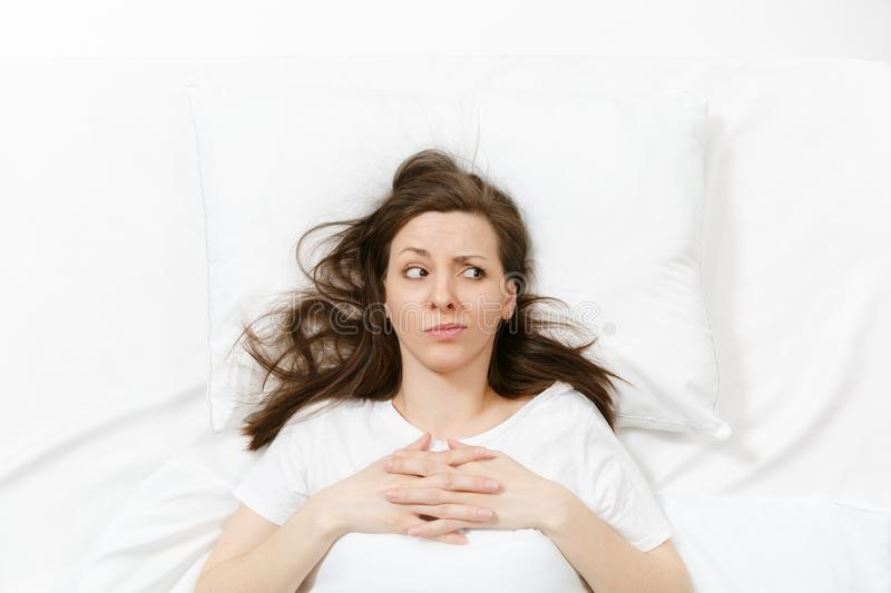 Top view of tired stressed crying young woman lying in bed with white sheet, pillow, blanket. Pensive frustrated sad royalty free stock image