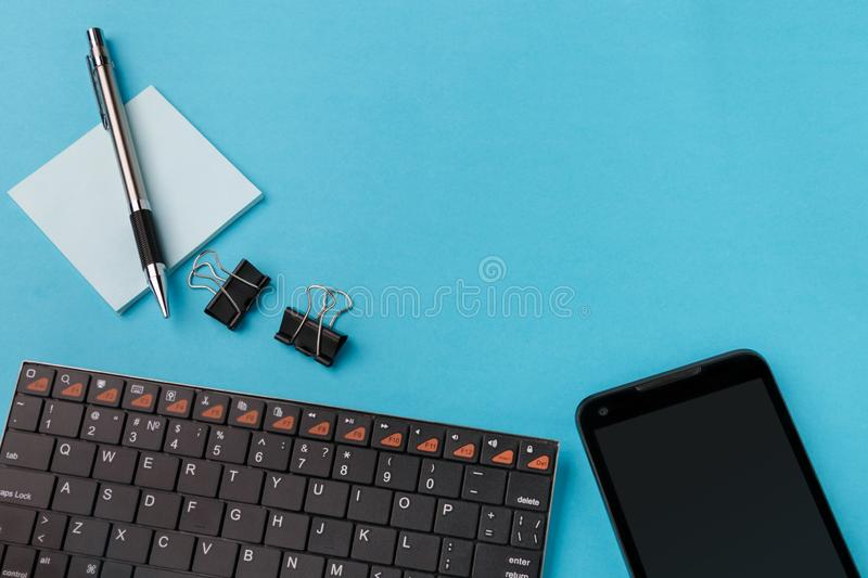 Workspace with wireless keyboard, smartphone, pen and stickers on cyan background. View from above stock photo