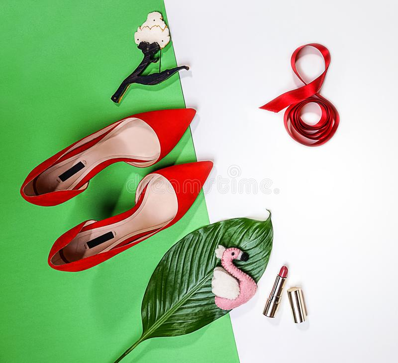 Top view to spring summer Valentine`s Day 8 March party outfit layout female red shoes accessories makeup tropical leaf and pink royalty free stock image