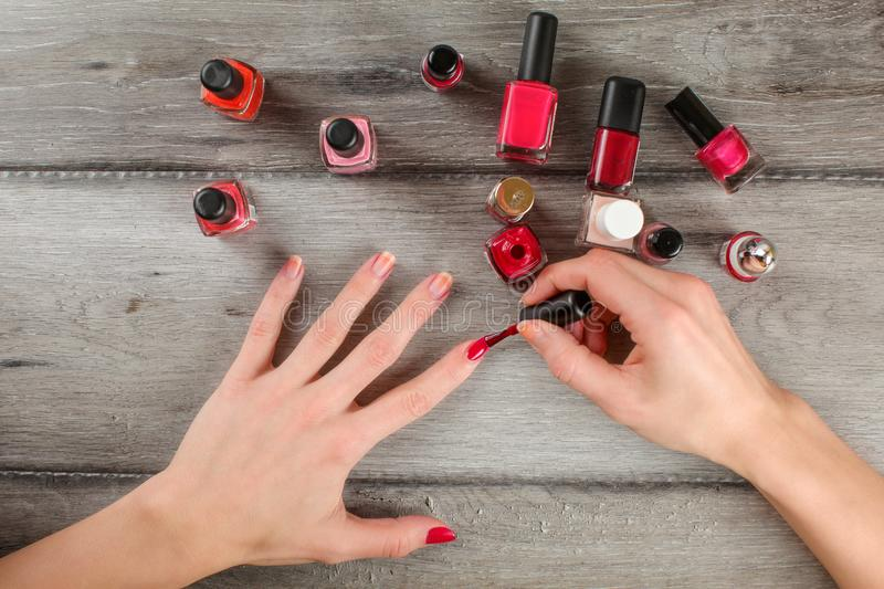 Top view to woman hands, applying coat of red nail varnish on he royalty free stock image