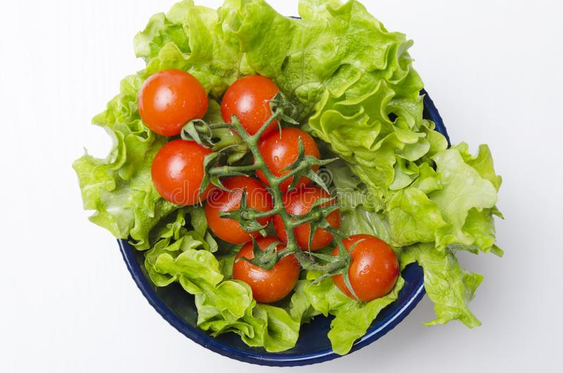 Top view of tomatoes and lettuce leaves in the bowl.Fresh and diet food for healthy life royalty free stock image