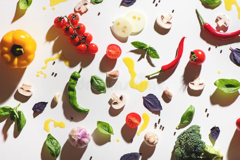 Top view of tomatoes, mashrooms, yellow pepper, chilli pepper, basil, garlic and spilled olive oil on white background. royalty free stock photography