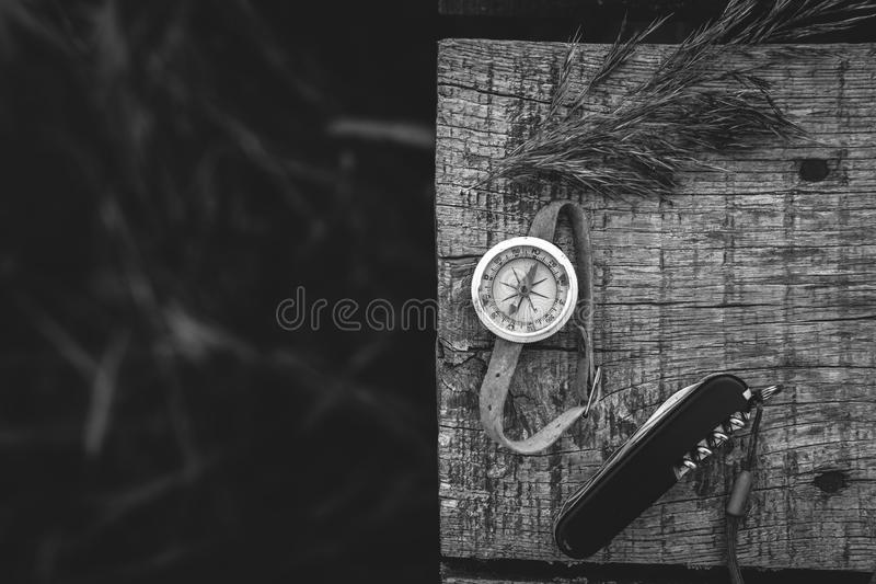 Top view on tourist stuff. multitool knife and old compass. survival kit. Dark autumn tones, space for text. gray wood background. Travel tourism concept stock photo