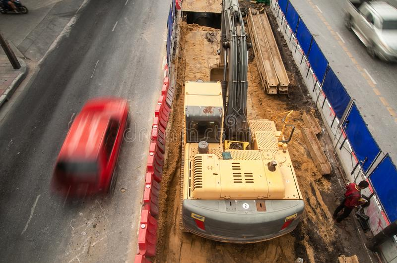 Top view, a tracked excavator on a construction site at traffic island, vehicle moving on an asphalt road royalty free stock images