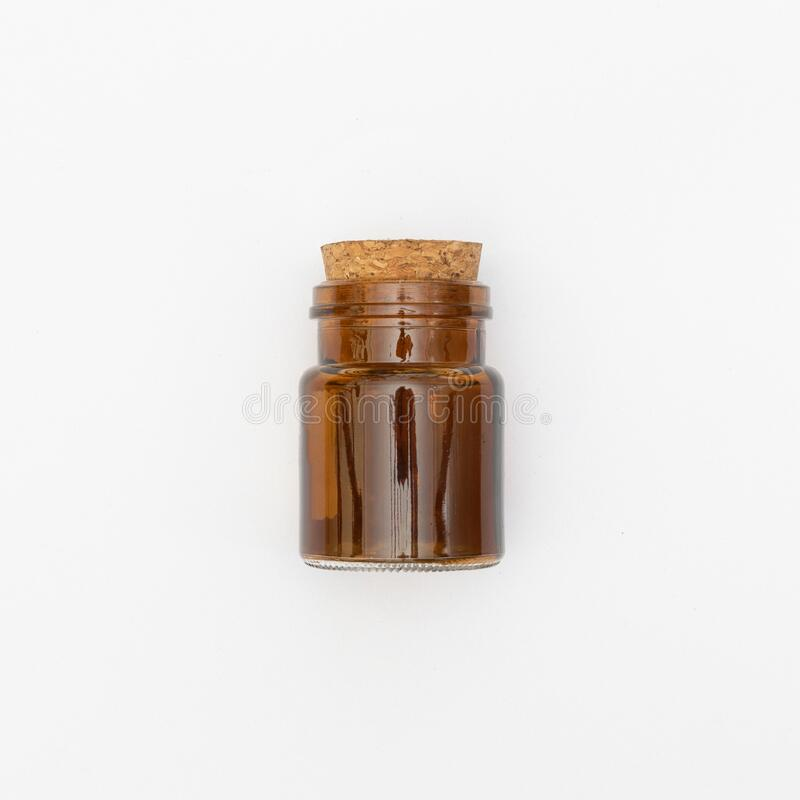 Top view of transparent empty brown glass jar bottle with closed cork cap lids on white background stock image