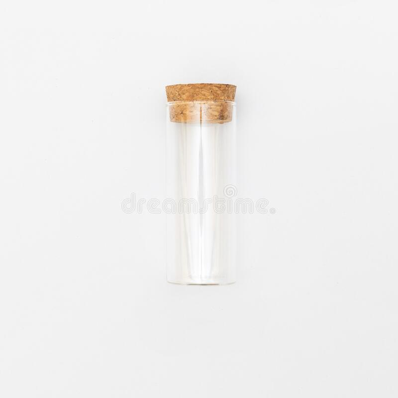 Top view of transparent empty glass jar or test tube bottle with closed brown cork cap lids on white background stock photo