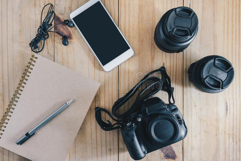 Top view of travel object : gray pencil on brown notebook. and white mobilephone, earphone, black camera and two lens on wooden ta stock images