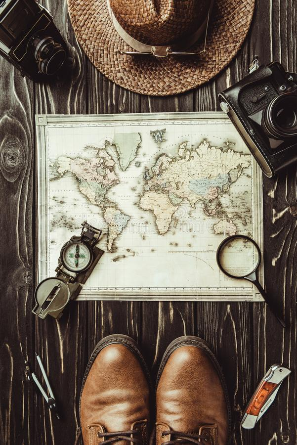 Top view of travel setting with straw hat, map, shoes, compass, magnifying glass and photo cameras on dark. Wooden surface royalty free stock photography