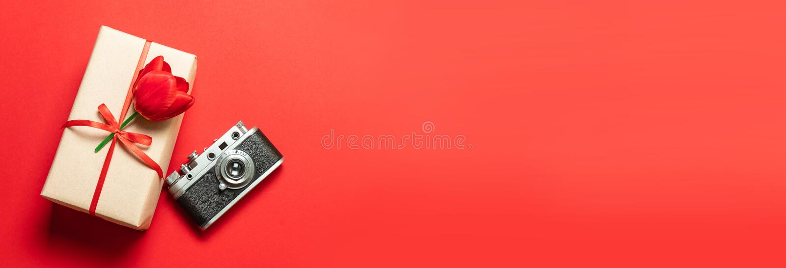 Top view of travel or vacation concept. Flat lay of the camera and a gift box with a red ribbon. T. Flat lay of the camera and a gift box with a red ribbon. Top royalty free stock image