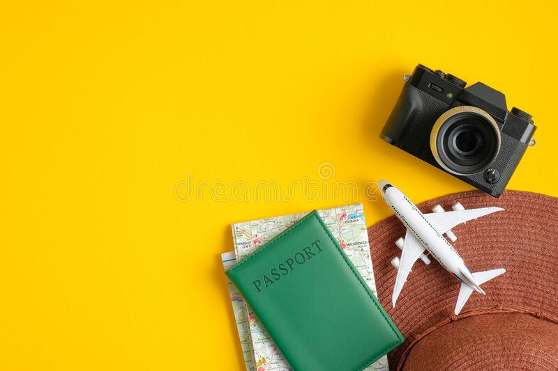 Top view of traveler accessories. Flat lay beach hat, passport, map, airplane, photo camera on yellow background with copy space. stock photography