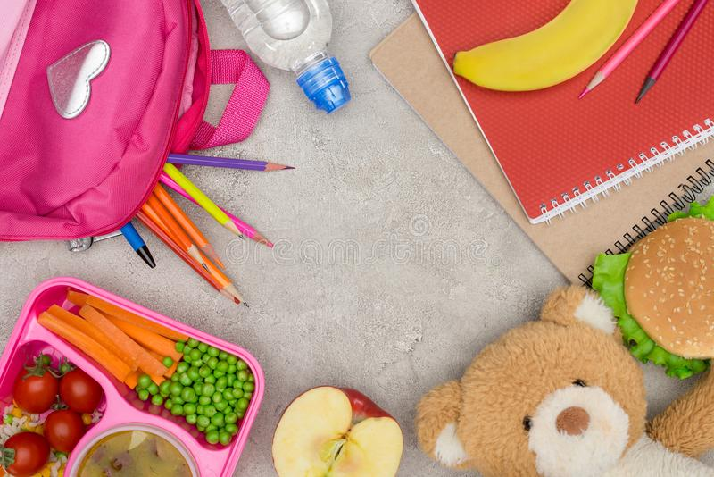 top view of tray with kids lunch for school, bag with pencils and notebooks stock photography