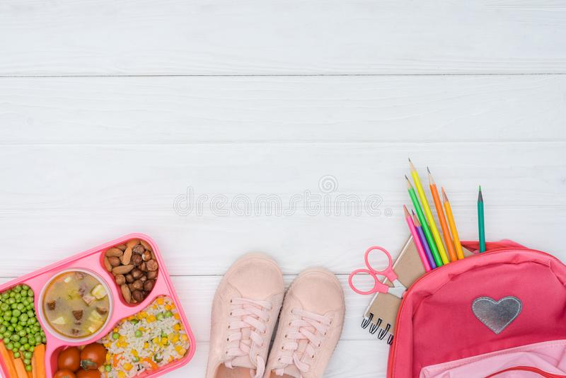 top view of tray with kids lunch, school bag with pencils and shoes royalty free stock image