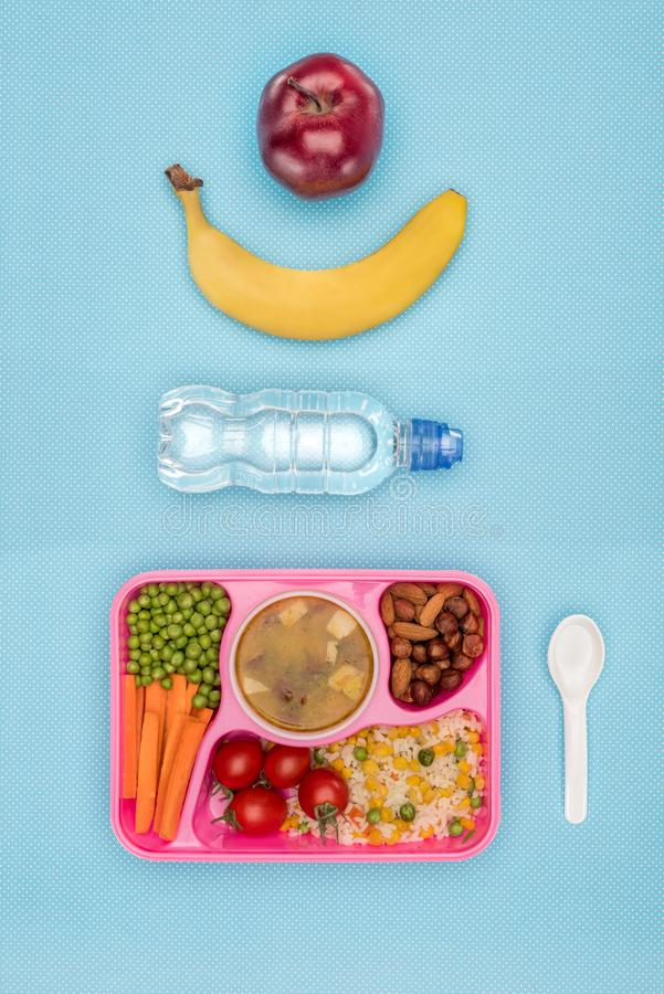 top view of tray with kids lunch for school, bottle of water, banana and apple stock image