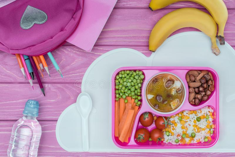 top view of tray with kids lunch for school, pink bag, pencils and bottle of water stock photo