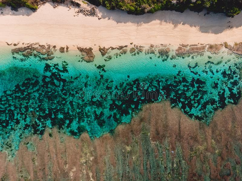 Top view of tropical beach with turquoise sea water and reef, aerial drone shot. Top view of tropical beach with turquoise sea water and reef, aerial drone photo stock image