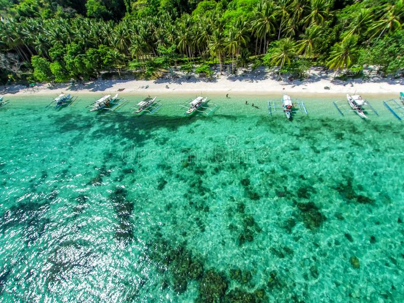 Top view of a tropical island with palm trees and blue clear water. Aerial view of a white sand beach and boats over a coral reef stock photography