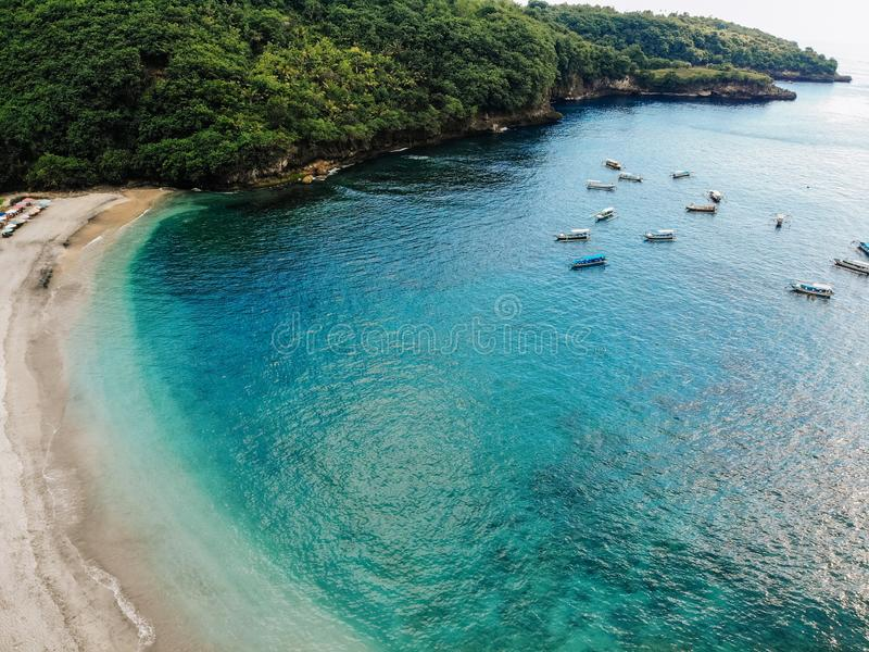 Top view of tropical island with white beach and blue clear water and jungle. Aerial view of bay with many boats and royalty free stock photo