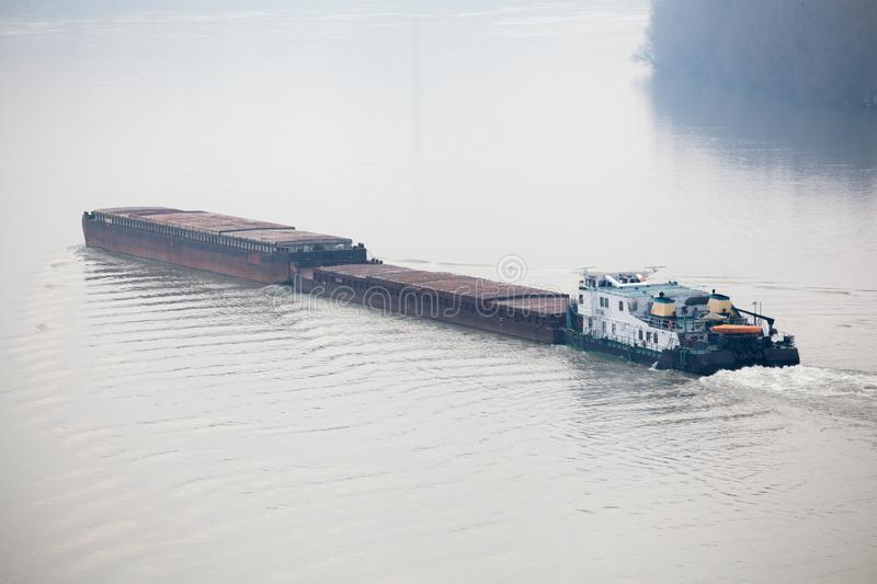Tugboat Pushing a Heavy Barge. Top view of Tugboat pushing a heavy barge on the river royalty free stock photos