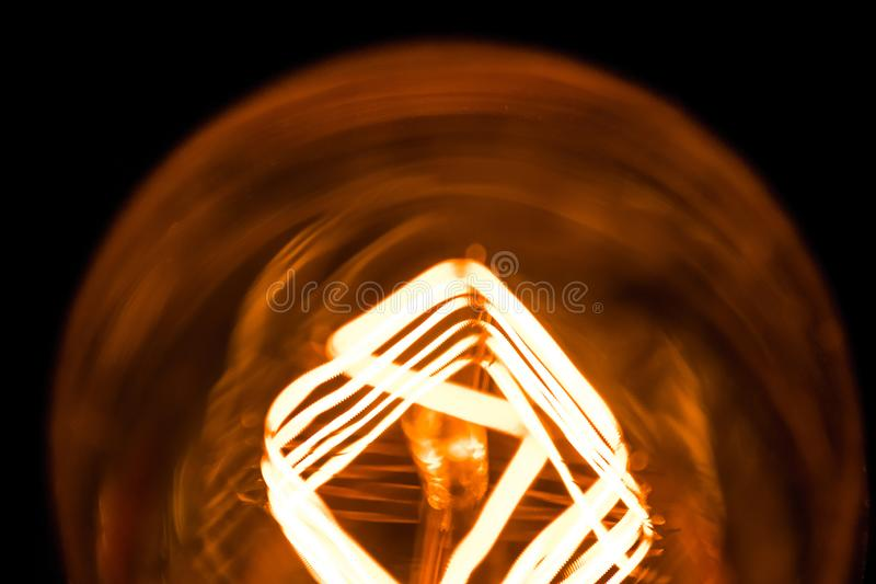 Top of view of turn on in slow motion with dust, retro vintage light bulb with old technology with filament built-in with warm royalty free stock photos