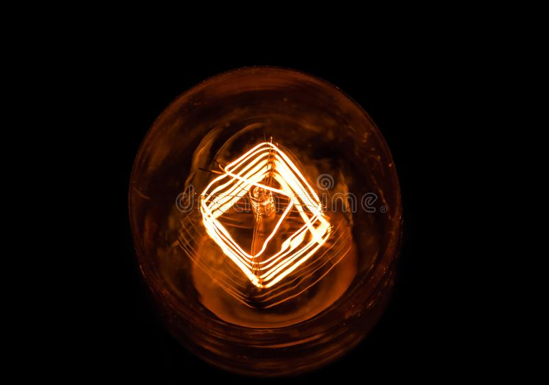 Top of view of turn on in slow motion with dust, retro vintage light bulb with old technology with filament built-in with warm royalty free stock photography