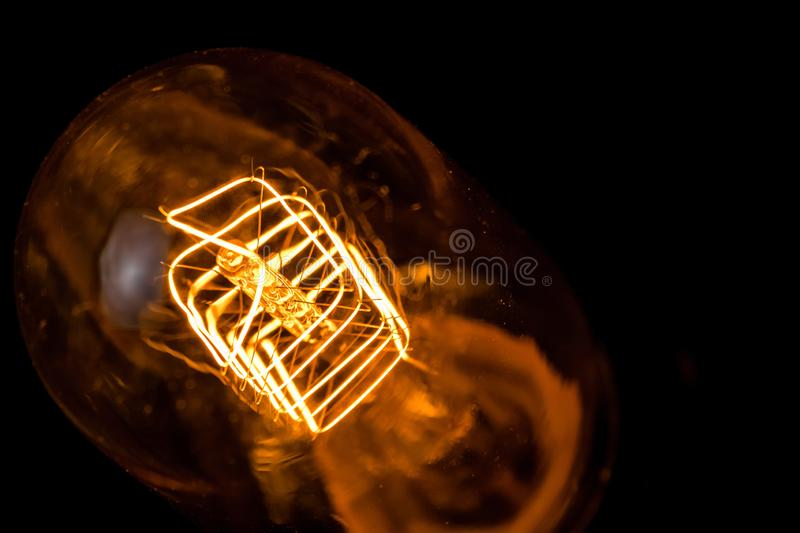 Top of view of turn on in slow motion with dust, retro vintage light bulb with old technology with filament built-in with warm stock photos