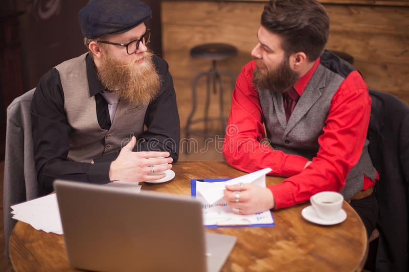 Top view of two bearded man having a meeting a coffeee shop. Top view of two bearded men having a meeting a coffeee shop. Stylish men. Handsome men. Long beard royalty free stock images