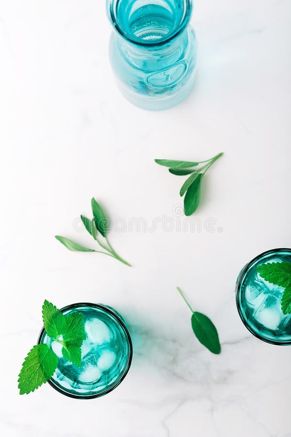 Top view of two beautiful vintage turquoise glasses and a bottle with cold drink and ice cubes, decorated with fresh green mint stock images