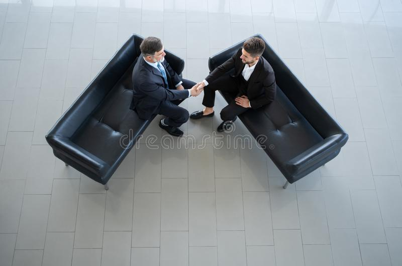 Top view of a two businessman shaking hands - Welcome to business. royalty free stock photo