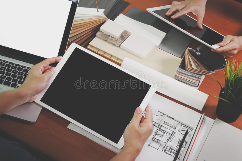 Top view of two colleagues interior designers discussing data. With blank screen new modern computer laptop and pro digital tablet with sample material on stock images