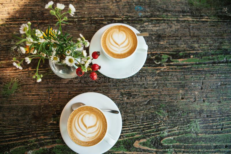 Top view of two cups of coffee and a vase of flowers on a wooden table. A photo means a meeting or a date. Top view of two cups of coffee and a vase of flowers stock image