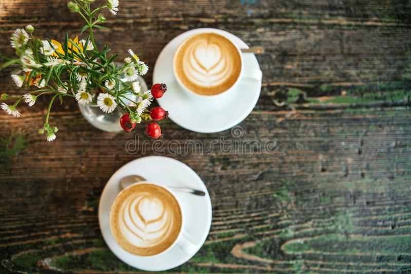 Top view of two cups of coffee and a vase of flowers on a wooden table. A photo means a meeting or a date. Top view of two cups of coffee and a vase of flowers stock photos