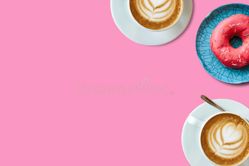 Top view. Two cups of fragrant delicious coffee cappuccino and a number of donut on a pink background. Nearby place for royalty free stock image