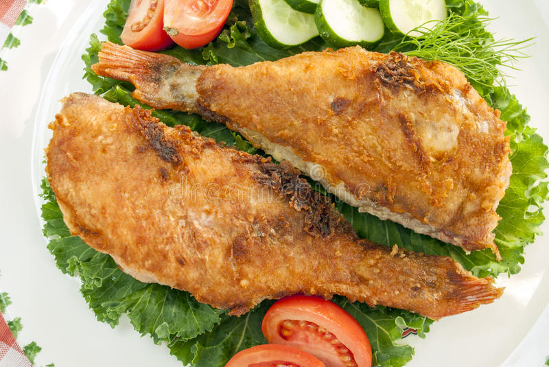 Top view of two fried sea bass with vegetables. Close-up stock image