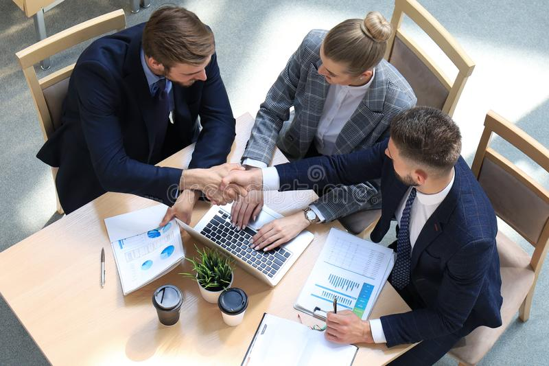 Top view of two men sitting at the desk and shaking hands while young woman looking at them and smiling. royalty free stock photo