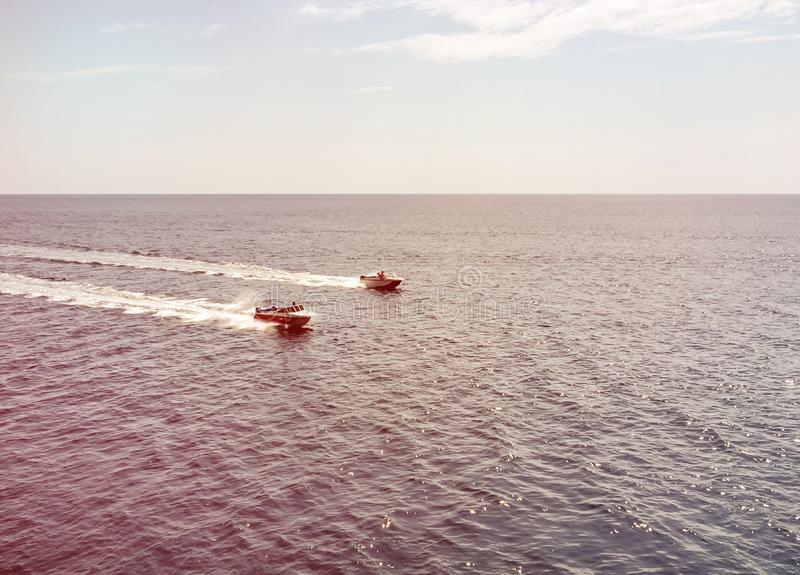 Top view on two white boats sail in blue sea and leave white streaks, compete in speed at sea, racing two boats royalty free stock photography