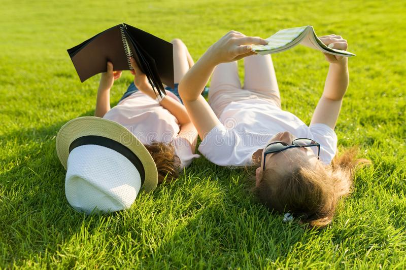 Top view, two young female students reading books lying on green grass. royalty free stock photos