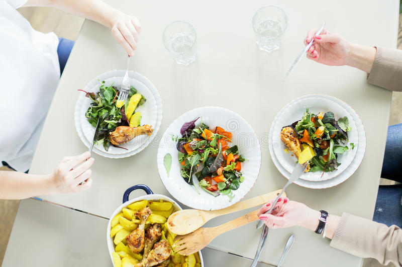 Top view of two young women eating green salads with chiken and potato royalty free stock photo