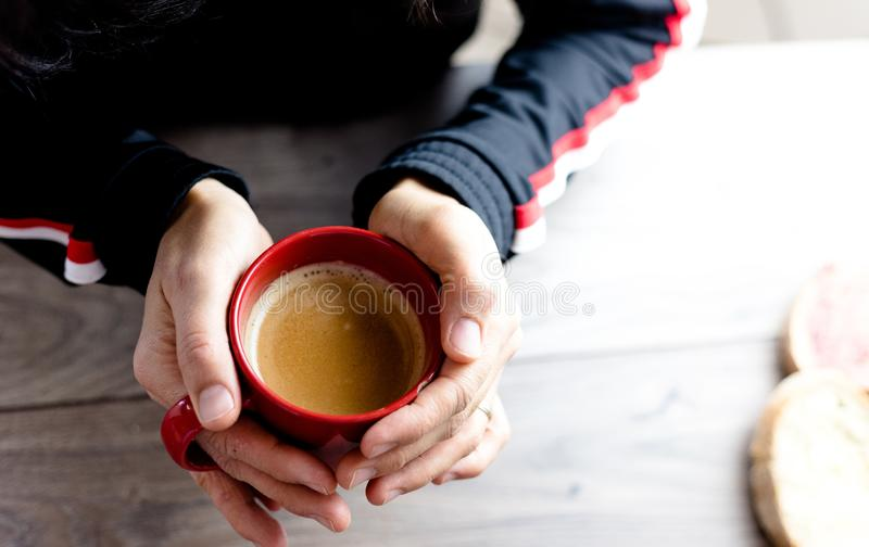 An unidentifiable person holding a red mug filled with coffee on a wooden rustic table royalty free stock photos