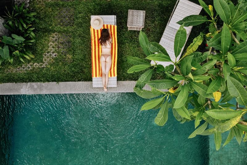 Top view of unrecognizable slim young woman in beige bikini relaxing and sunbathe near luxury swimming pool in green. Tropic in Bali.Vacation concept. Drone royalty free stock images