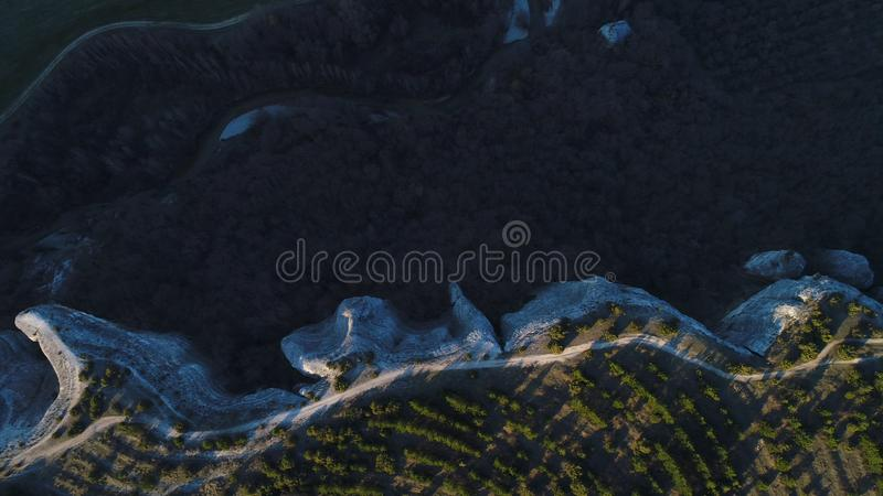 Top view of unusual forms of volcanic cliffs in New Zealand. Shot. Aerial for beautiful stone rocks and green trees with royalty free stock photography