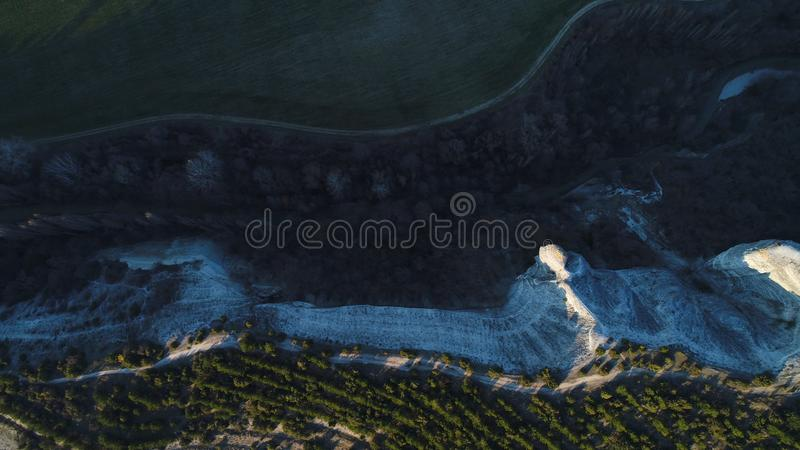 Top view of unusual forms of volcanic cliffs in New Zealand. Shot. Aerial for beautiful stone rocks and green trees with stock images