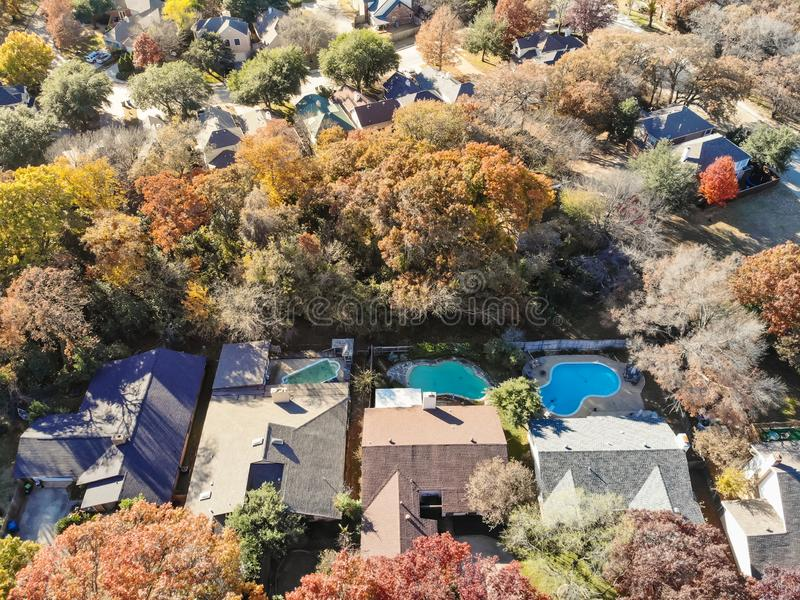 Aerial view rich houses with swimming pool in autumn near Dallas, Texas. Top view upscale neighborhood with luxury house and swimming pools surround by colorful stock image