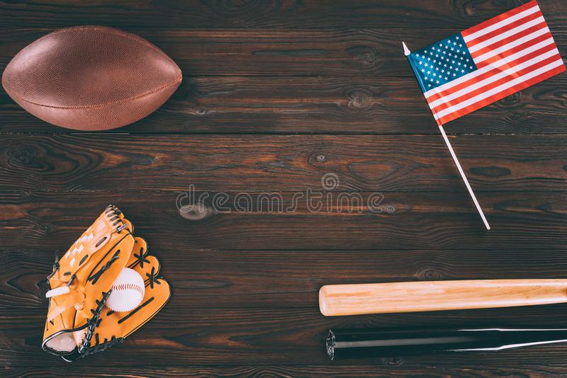 Top view of us flag, rugby ball, baseball bats and glove with ball. On wooden table royalty free stock photos