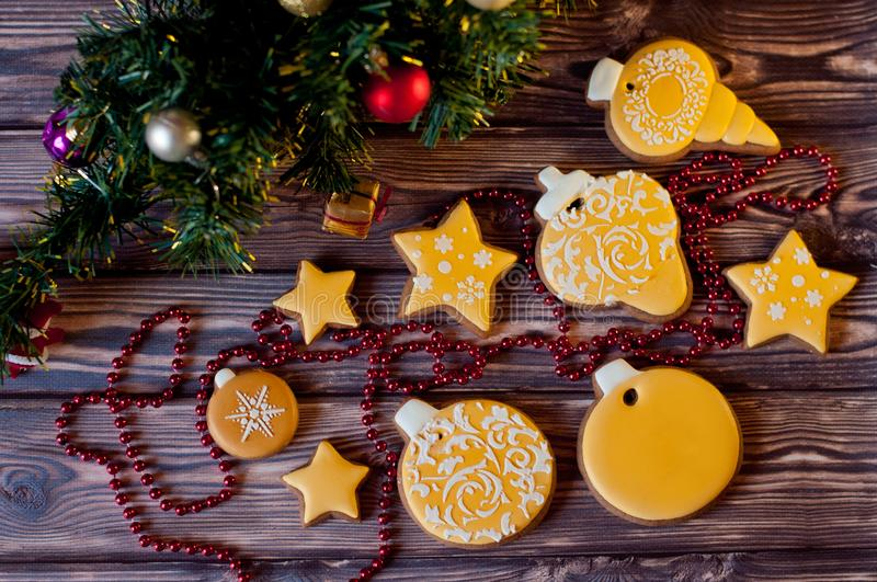 Top view on variety of yellow glazed ginferbread cookies laying near christmas decorations on wooden background stock photos