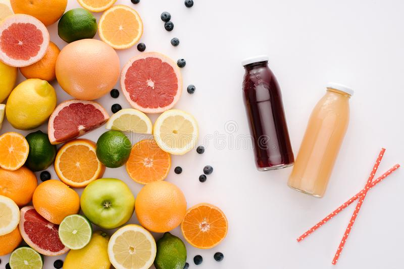 top view of various citrus fruits and blueberries with bottles of juice royalty free stock photos