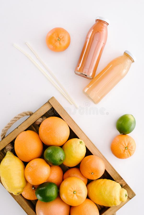 top view of various citrus fruits in wooden box with bottles of juice stock photography