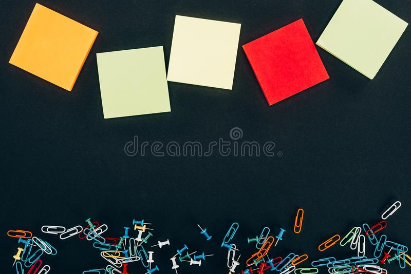 Top view of various colorful blank notes and paper clips. On black stock images