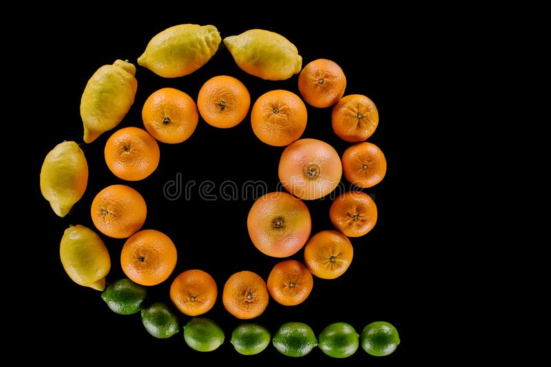 Top view of various fresh citrus fruits composition in spiral shape. Isolated on black royalty free stock images